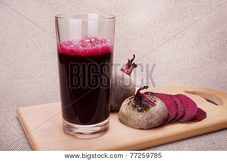 Beetroot juice near sliced fresh beetroot