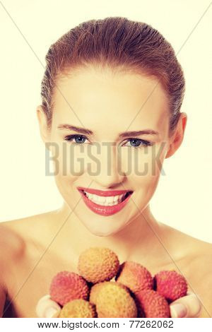 Beautiful topless caucasian woman holding fist of lychee.  Isolated on white.