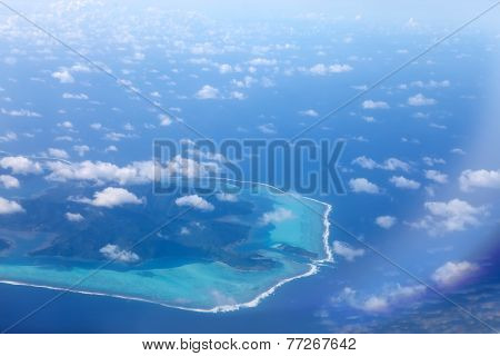 Polynesia. The atoll in ocean through clouds. Aerial view.