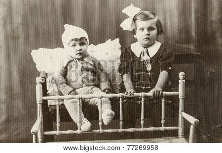 POLAND, CIRCA 1930s - Vintage photo of little girl and baby brother