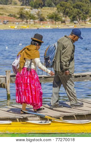 COPACABANA, BOLIVIA, MAY 7, 2014: Local woman in traditional attire walk with her husband on jetty in port (Titicaca lake)