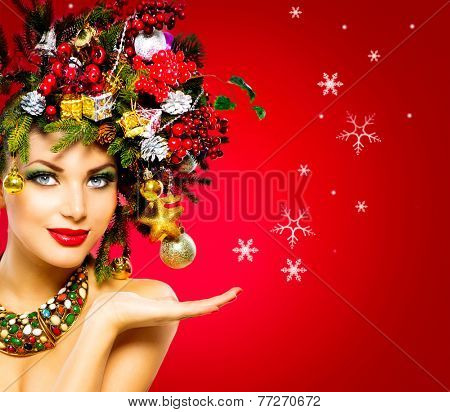 Christmas Winter Woman. Beautiful New Year and Christmas Tree Holiday Hairstyle and Make up. Beauty Fashion Model Girl over holiday red Background. Creative Hair style decorated with Baubles. Hand