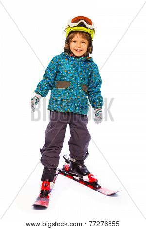 Boy wearing skies stands on white background
