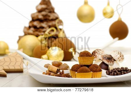 Christmas Sweets, Meringue And Chocolate Bauble With Christmas Chocolate Tree In The Background