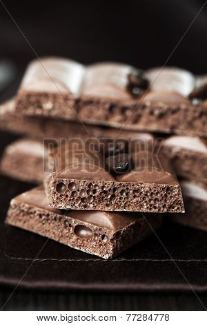 Tasty porous chocolate with coffee beans on table, close up