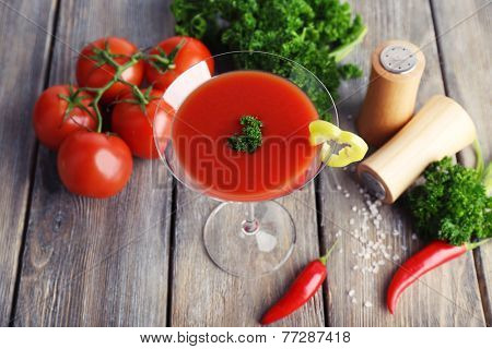 Tomato juice in goblet and fresh vegetables on wooden background