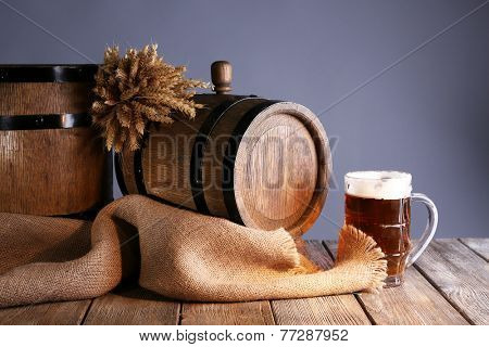 Beer barrel with beer glass on table on grey background