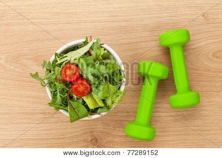 Dumbells and healthy food over wooden table. Fitness and health