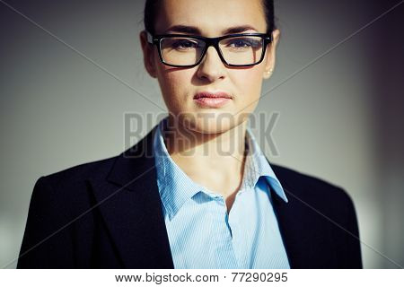 Serious formally dressed businesswoman in eyeglasses