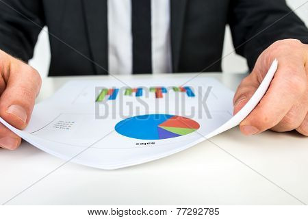 Businessman Analysing A Set Of Bar And Pie Graphs