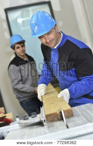 Carpenter showing trainee how to use electric saw