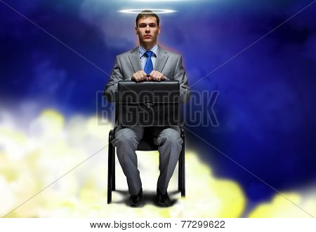 Young businessman with halo above head sitting on chair