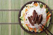 pic of rice noodles  - Delicious Asian salad rice noodles and meat with chopsticks - JPG