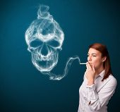 picture of smoking woman  - Pretty young woman smoking dangerous cigarette with toxic skull smoke  - JPG