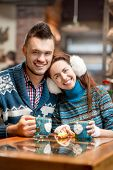 picture of iroquois  - Young loving couple dressed in blue sweater sitting with knitted coffee cups in the cafe in winter - JPG