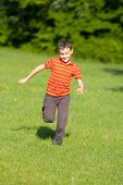 Cute Kid Running On Grass