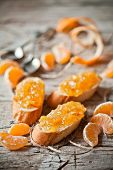 image of baguette  - pieces of baguette with orange marmalade closeup on rustic wooden board - JPG