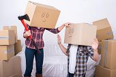 stock photo of ax  - Cheerful young couple with cardboard boxes on their heads - JPG