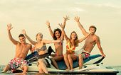 picture of jet-ski  - Group of happy multi ethnic friends sitting on a jet ski - JPG