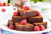 stock photo of brownie  - Homemade chocolate brownies decorated with fresh raspberry - JPG