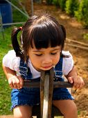 picture of seesaw  - 2-year-old Asian-Caucasian girl plays on a seesaw