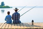 stock photo of father child  - boy and his father fishing together from a pier - JPG