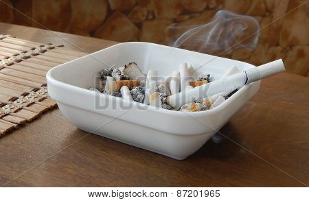 Ashtray with smoke cigarette and butts