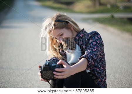 Cute blonde woman taking self portrait with a cat