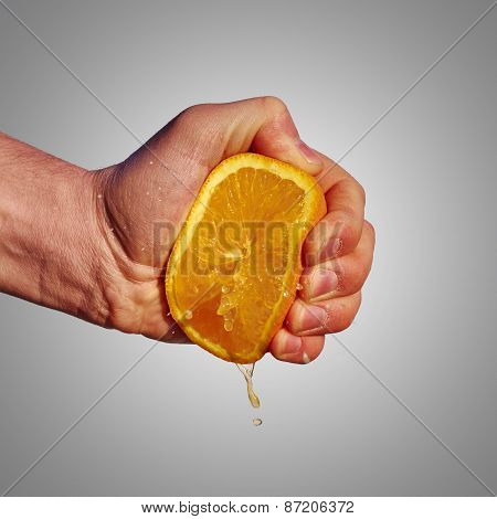 Man's Hand Squeezes The Juice From The Orange