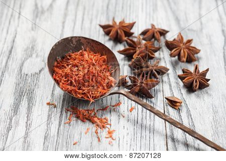 saffron in old spoon with anise on wooden background
