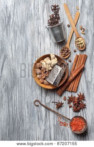 Various spices on wooden background - anise, cardamon, cinnamon, ginger, clove, nutmeg, papper and saffron
