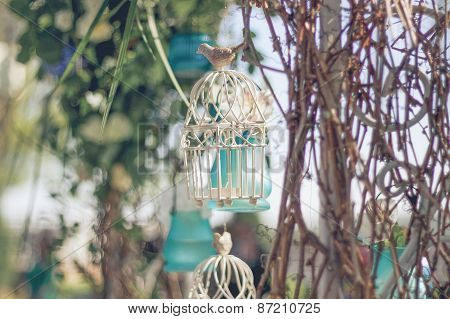 White decorative cage with beautiful flowers, suspension cells
