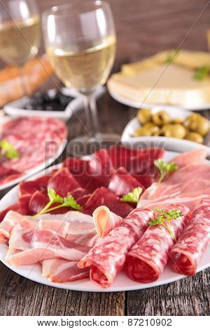 plate with meats and wine glass