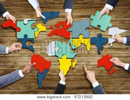 Business People Forming World Map with Puzzle Pieces