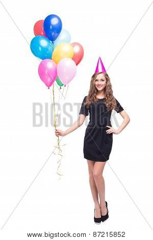 Happy woman with birthday hat and colourful balloons