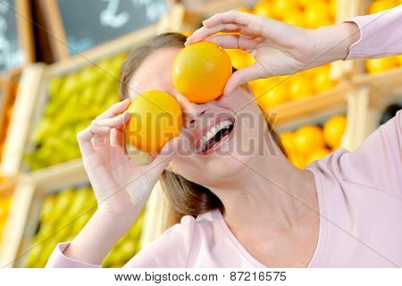 Playful woman covering her eyes with oranges