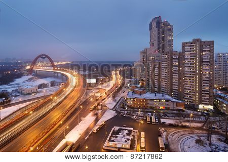 Urban highway, bridge over river and residential district of Moscow in winter night. Long exposure