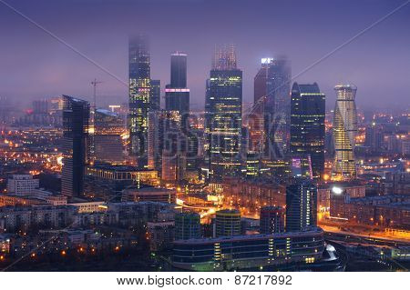 Skyscrapers of Moscow City business complex in fog at night in Moscow, Russia