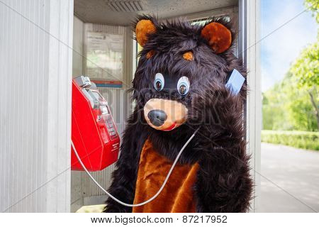 actor dressed as bear talks on red public telephone