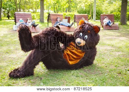 actor dressed as bear lies on grass in park and people on loungers with gadgets