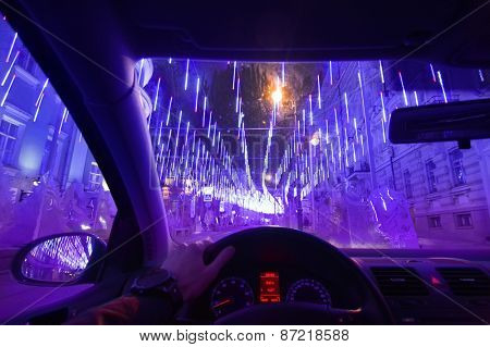 Hands of driver and windshield on street decorated with illuminations in winter night