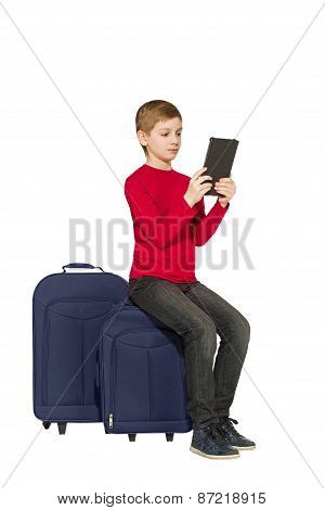 Boy Sitting On Travel Bags Using Tablet Isolated On White