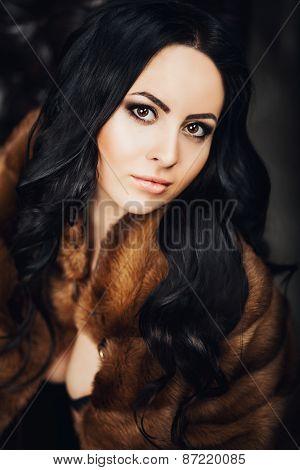 beautiful brunette girl with beautiful dark eyes in a fur coat