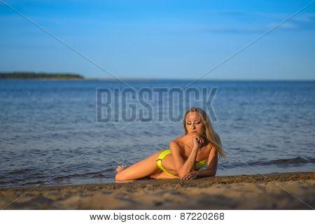 young woman in green bikini posing on a beach