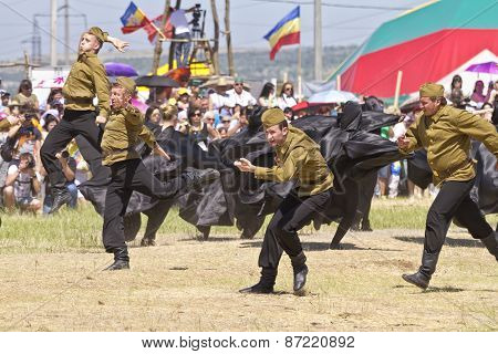 Dancing group in folk costumes and the form of the Soviet army at the festival Sabantui-2014