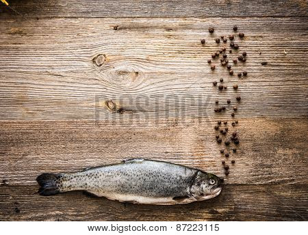 Fresh trout with dried peppers on a dark wooden table