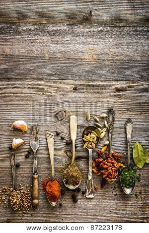 seasonings and spices in the spoons on a brown wooden table
