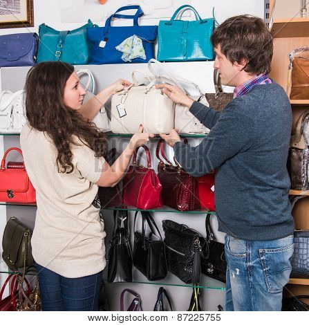 Shop assistant showing white leather bag to beautiful girl