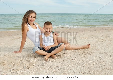 Mother And Her Son Having Fun On The Beach