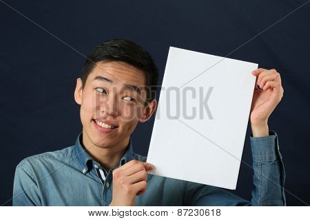 Funny young Asian man showing white copy space page and looking sideways